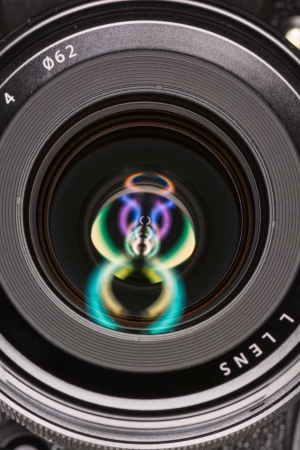 Macro shot of front element of a camera lens with beautiful color lights reflections  Stock Photo