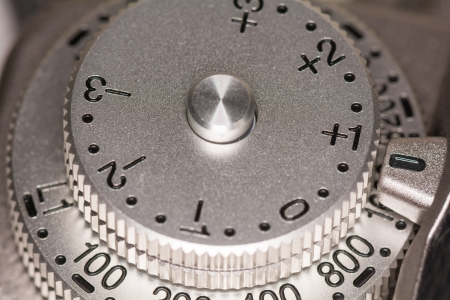Exposure compensation dial on a old style single lens reflex SLR camera set to plus one
