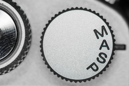 Manual, Aperture priority, shutter priority, and program auto mode dial on a DSLR camera set on Aperture priority mode