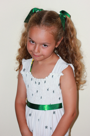 Smiling pretty curly little girl in white dress