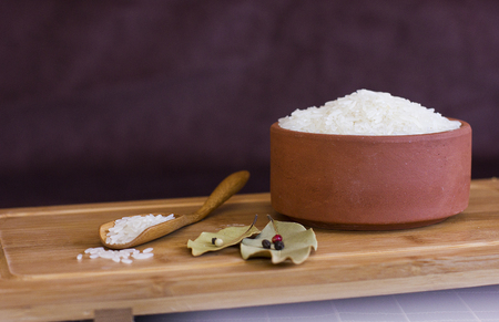 White rice in a clay bowl and in the wooden spoon. Bay leaves and black peppercorns.