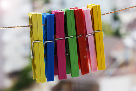 Colorful clothespins hanging on rope on a city background Stock Photo