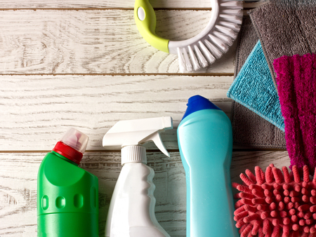 Colored microfiber napkins, cleaning agent, spray and brush on the white floor.