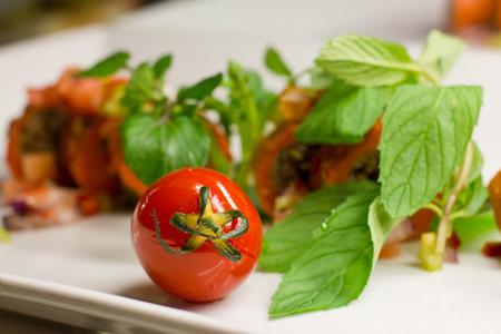 Cherry tomato with fresh vegetables and mint on white plate Stock Photo