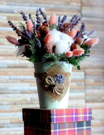 Bouquet of lavender, pink flowers, fir branches, hazelnuts and cotton in a white pot against the backdrop of stone wall