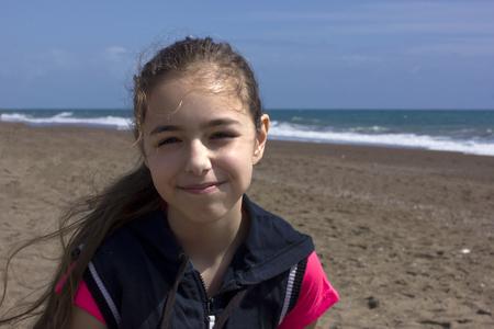 Młoda dziewczyna siedzi na plaży w pobliżu błękitnego morza Zdjęcie Seryjne