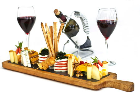 Cheese plate: roquefort with blue mold, cheddar, smoked cheese, mozzarella on a wooden board. Decorated with bread sticks