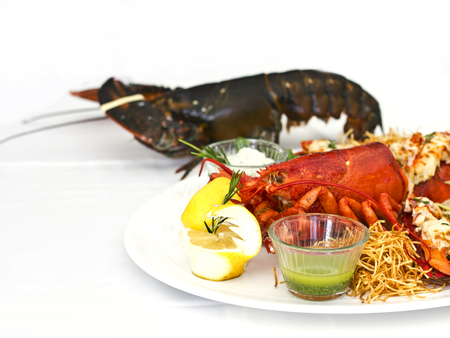 Live and cooked lobster served with the vegetables on a white plate. Isolated