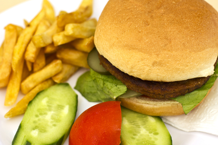 Hamburger with the French fries, sliced cucumbers and tomatoes