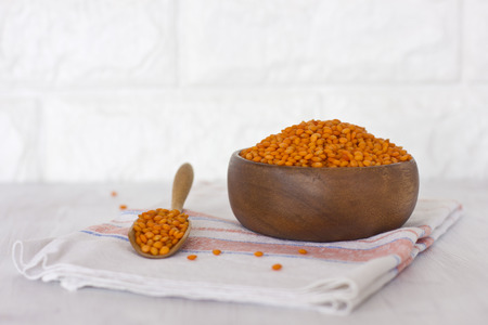 Raw red lentils in a wooden bowl and spoon on linen napkin on a white table Archivio Fotografico