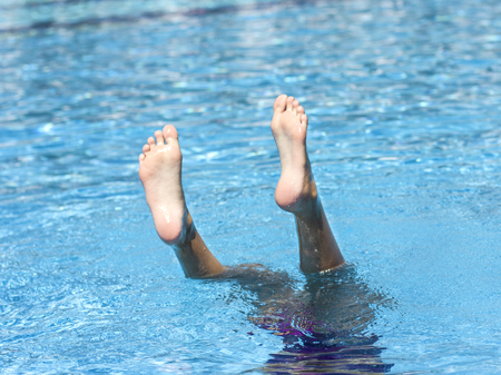 Foot of a girl diving into the water, sticking out of pool