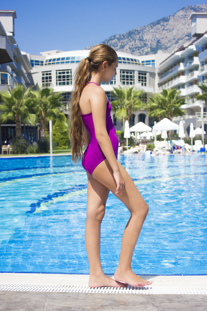 Beautiful teenage girl in purple swimsuit standing at poolside 免版税图像