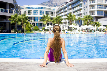 KEMER, ANTALYA, TURKEY - 19 JULY, 2018: Beautiful teenage girl in the purple swimsuit sitting at poolside