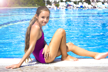 Beautiful teenage girl in purple swimsuit sitting by the poolside and smiling to camera