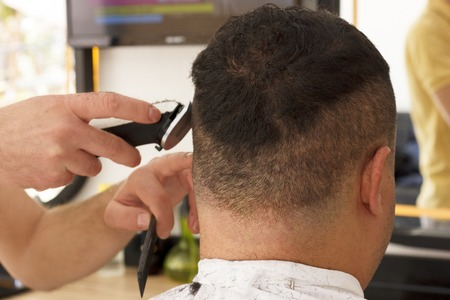 Back view of man getting short hair trimming at barber shop with a clipper machine