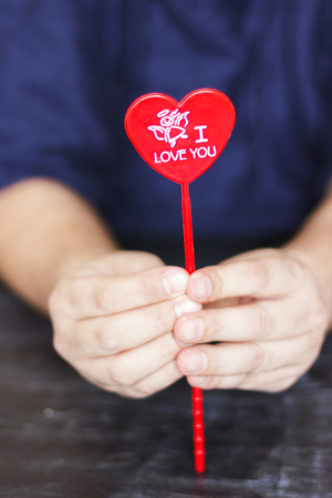 Man holds red heart with the words I love you in his hands