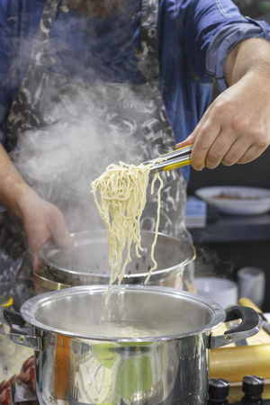 Chef takes out with slotted spoon hot steaming egg noodles from pan