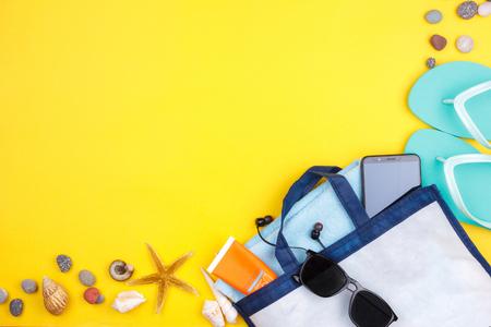 Sun glasses, sun screen, headphones, smartphone, towel, slippers Flatlay beach vacation on yellow background
