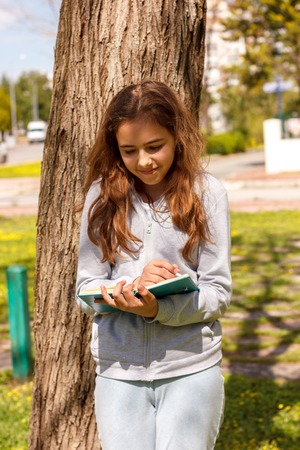Cute teen girl writes with pen in a notebook near in a park