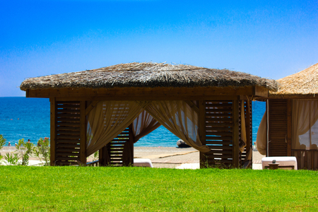 Pavilion with a thatched roof on sandy beach. Mediterranean summer and sea 免版税图像