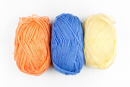 Flatlay of multicolored pastel knitting skeins of yarn and knitting needles on a white background Фото со стока