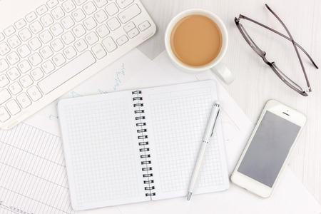 Flat lay of white office desk with laptop, smartphone, eyeglasses, notebook and pen with copy space background. Mockup