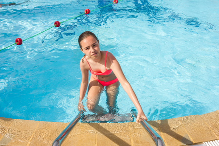 Young teen girl swims and having fun in the outdoor pool