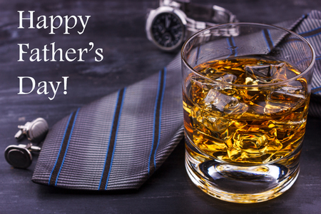 Male concept for father's day. Tie, watches, cufflinks and glass of whiskey with ice. Lettering - Happy father's day