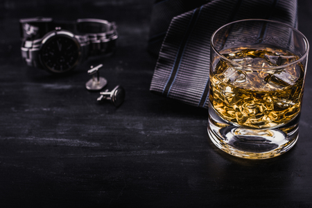 Male concept for father's day. Tie, watches, cufflinks and glass of whiskey with ice Stock Photo