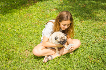 Beautiful teen girl watching a funny video on a smartphone with her pug dog in a summer park