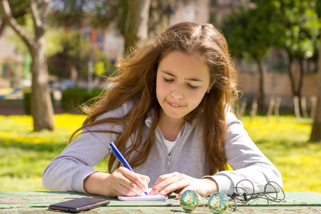 Cute teen girl writes notes on a paper pad by wooden table on green meadow