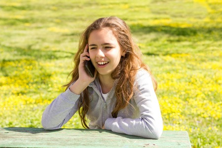 Pretty teenager girl with mobile cell smartphone at summer park Stok Fotoğraf
