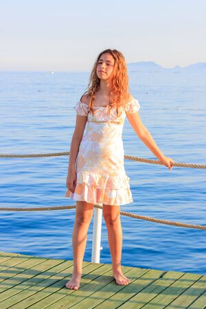 Cute teen girl in dress and with long hair on pier by the sea Stok Fotoğraf