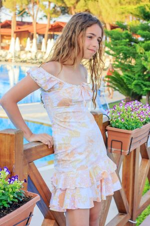 Cute teen girl in romantic dress and with long hair is standing on the bridge by the pool