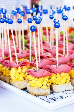 Canapes with corn, ham sauce on a white plate