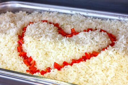 Boiled rice decorated with heart of red pepper