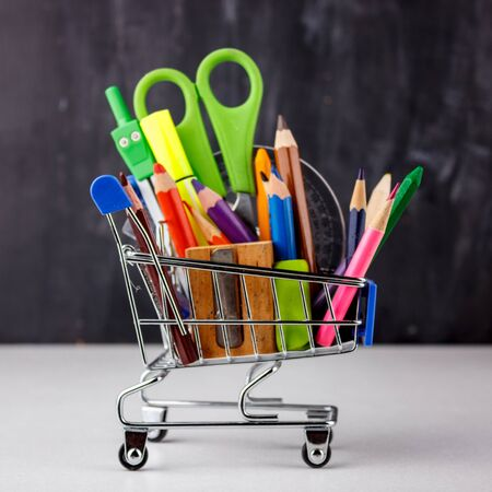 Set of colored pencils and markers for school. Stationery for the student - scissors, sharpener, eraser in shopping cart