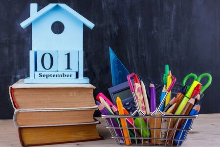 Set of colored pencils and markers for school in a shopping cart. 1 of September calendar on pile of books