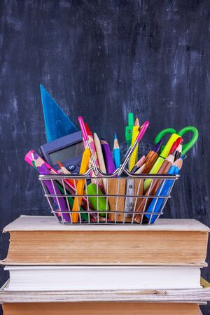 Set of colored pencils and markers for school. Stationery for the student - scissors, sharpener, eraser near by pile of books and alarm clock Stok Fotoğraf