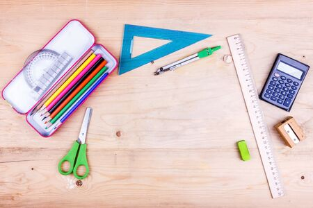 Back to school concept. Flat lay of stationery for the student - scissors, sharpener, eraser and white notebook.