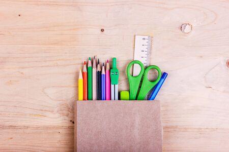 Concetto di scuola. Matite colorate, forbici, righello, compassi in un sacchetto di carta marrone Archivio Fotografico