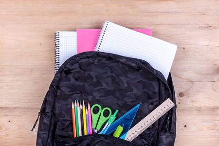 Black school bag with set of stationery for the student and with white notebook in it. Back to school concept