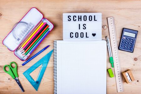 Back to school concept. Flat lay of stationery for student - scissors, sharpener, eraser and white notebook. School is cool lettering