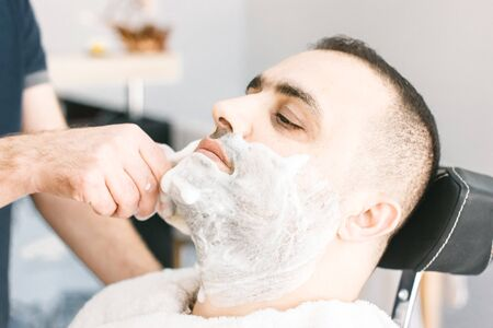 Hairdresser shaves a beard to a man with a razor in a barbershop