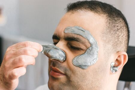 Male face waxing. Barber removes hair by shugaring from face of turkish man.