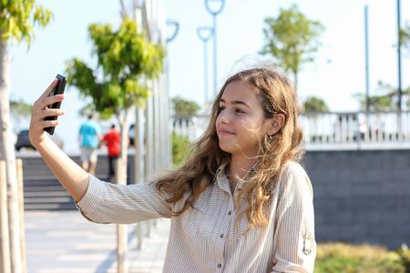 Schönes Teenagermädchen, das an einem sonnigen Tag ein Selfie auf der Promenade macht. Glückliches junges Mädchen, das mit Smartphone in ihren Händen lächelt Standard-Bild