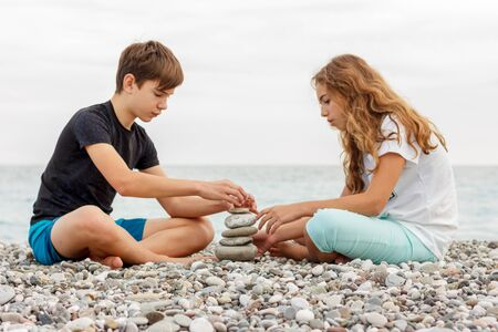 Couple of beautiful teens, first love. Girl and boy sitting at the beach and playing with pebble stones
