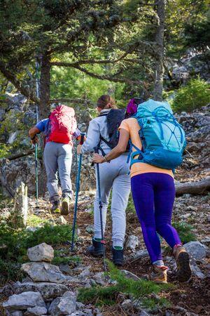 Bergsteigen. Mit den Trekkingstöcken und Rucksäcken geht es zu dritt bergauf. Standard-Bild