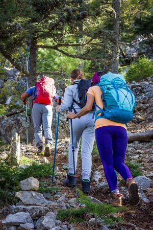 Mountain climbing. Three people go uphill with the trekking poles and backpacks. Reklamní fotografie