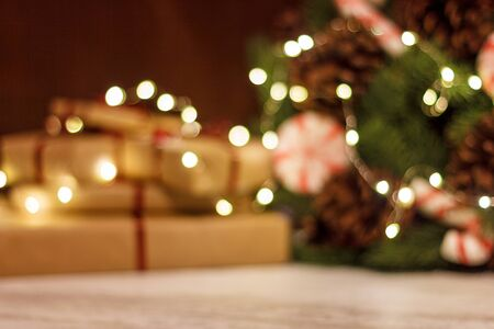 Gift boxes and Christmas wreath with luminous garland. Blurred background without focus with bokeh
